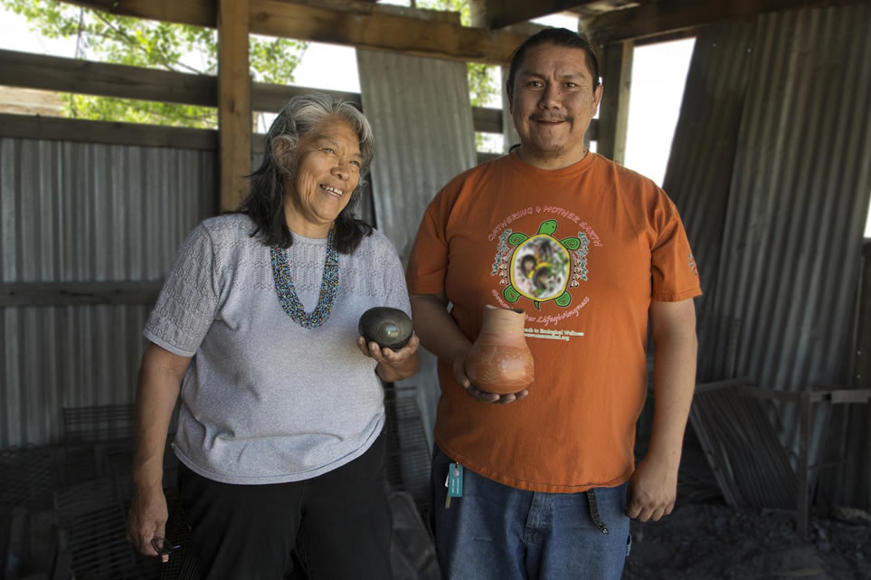 Kathy Wan Povi Sanchez and Wayland Sanchez stand in a an outdoor structure holding their pottery.