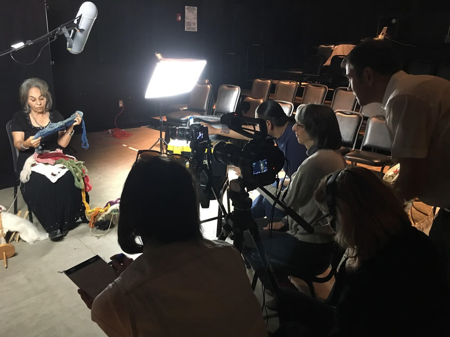 A group of people stand behind a camera filming while a woman sits under a light being filmed.