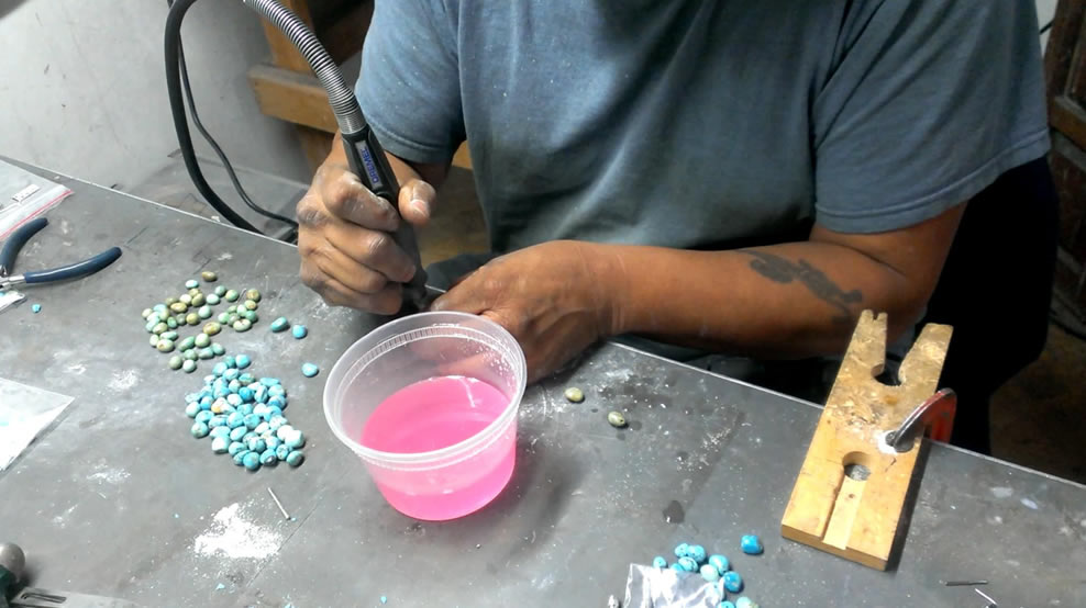 A jeweler's hands hold a tool atop a workbench with turquoise stones.